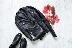 concepto de moda Chaqueta de cuero negra, zapatos negros y hojas del rojo imagen de archivo libre de regalías