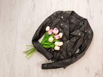 concepto de moda Chaquetas de cuero negras, tulipanes en un fondo de madera fotografía de archivo libre de regalías