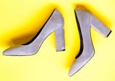 Concepto de moda de los zapatos Zapatos hechos fuera del ante gris en fondo amarillo Pares de zapatos de tacón alto de moda Fotos de archivo