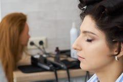 Concepto de moda y de belleza La morenita hermosa con el pelo enorme se preparó para el trabajo de un estilista foto de archivo