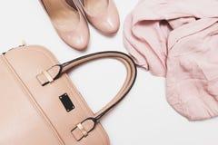 Concepto de moda, zapatos beige en colores pastel con las altas colinas, bolso de cuero y blusa delicada en el fondo blanco, vent fotos de archivo