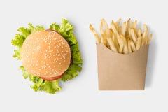 Concepto de mofa encima de la hamburguesa y de las patatas fritas en el fondo blanco Foto de archivo libre de regalías
