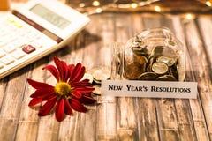 Concepto de motivación de los ahorros del tarro del dinero de la resolución del ` s del Año Nuevo en el tablero de madera Foto de archivo libre de regalías