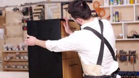 Concepto de negocio y de fabricaci?n El hombre joven en el taller monta los muebles