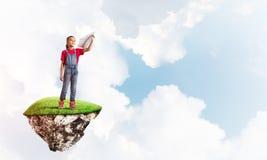 Concepto de niñez feliz descuidada con el avión de papel que lanza de la muchacha Foto de archivo
