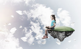 Concepto de niñez feliz descuidada con el libro de lectura de la muchacha Imágenes de archivo libres de regalías