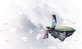 Concepto de niñez feliz descuidada con el libro de lectura de la muchacha Imagenes de archivo
