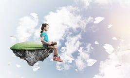 Concepto de niñez feliz descuidada con el libro de lectura de la muchacha Fotografía de archivo