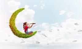 Concepto de niñez feliz descuidada con la muchacha en la luna verde foto de archivo