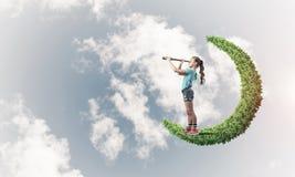 Concepto de niñez feliz descuidada con la muchacha en la luna verde fotos de archivo