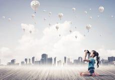 Concepto de niñez feliz descuidada con la muchacha que mira en binocul Foto de archivo libre de regalías