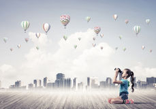 Concepto de niñez feliz descuidada con la muchacha que mira en binocul Imagen de archivo