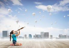 Concepto de niñez feliz descuidada con la muchacha que mira en catalejo Imagen de archivo libre de regalías