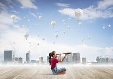 Concepto de niñez feliz descuidada con la muchacha que mira en catalejo Foto de archivo libre de regalías