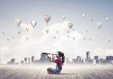 Concepto de niñez feliz descuidada con la muchacha que mira en spyglas Imagenes de archivo