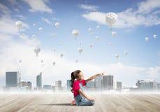 Concepto de niñez feliz descuidada con la muchacha que señala en algo Fotos de archivo
