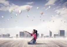 Concepto de niñez feliz descuidada con la muchacha que señala en el someth Imagen de archivo