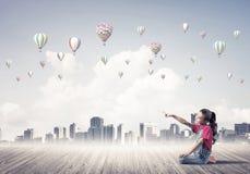 Concepto de niñez feliz descuidada con la muchacha que señala en el someth Imagen de archivo libre de regalías