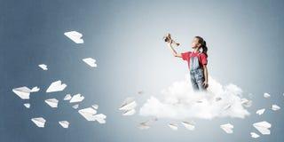 Concepto de niñez feliz descuidada con la muchacha que sueña para convertirse Fotos de archivo libres de regalías