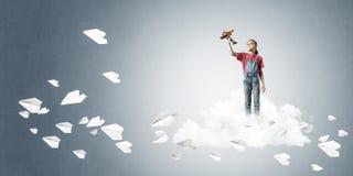 Concepto de niñez feliz descuidada con la muchacha que sueña para convertirse Imagen de archivo libre de regalías