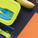 Concepto de nuevo a los efectos de escritorio de la caja del almuerzo del plátano del reloj de la escuela en fondo negro Foto de archivo libre de regalías
