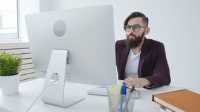 Concepto de oficina el trabajar independientemente y del trabajo Empleado elegante joven que mira el monitor de computadora duran almacen de metraje de vídeo