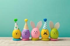 Concepto de Pascua con los huevos, el conejito, los polluelos y los sombreros hechos a mano lindos del partido Imágenes de archivo libres de regalías