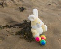 Concepto de Pascua, conejo del peluche con los huevos coloreados en la playa, VAC Imagen de archivo libre de regalías