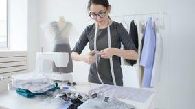 Concepto de pequeña empresa y de pequeña producción La mujer bonita joven de la modista cose la ropa en el taller almacen de video