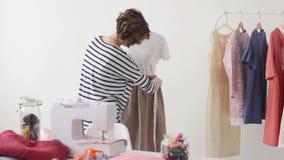 Concepto de pequeña empresa y de pequeña producción La mujer bonita joven de la modista cose la ropa en el taller metrajes