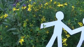 Concepto de persona y de ambiente Figuras humanas hechas del papel en hierba Cámara de la cámara lenta del panorama de la gente almacen de video