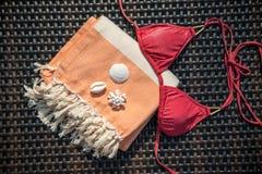 Concepto de primer de los accesorios del verano de la toalla turca anaranjada y blanca, del top bikini y de las conchas marinas b Fotografía de archivo