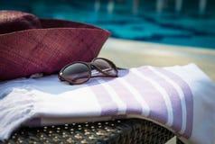 Concepto de primer de los accesorios del verano de la toalla turca, de gafas de sol y del sombrero de paja púrpuras y blancos en  Fotografía de archivo libre de regalías
