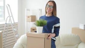 Concepto de propiedades inmobiliarias y de vida sola Mujer joven feliz que se mueve al nuevo hogar almacen de metraje de vídeo