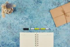 Concepto de registrar sus asuntos diarios en su mesa Libreta en un fondo abstracto azul Copie la disposición del espacio Lugar pa imagen de archivo