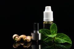 Concepto de sabores de la nuez y de la menta para los cigarrillos electrónicos en un fondo negro imágenes de archivo libres de regalías