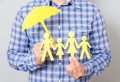 Concepto de seguro de la familia con el paraguas que protege a una familia Foto de archivo