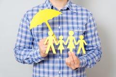 Concepto de seguro de la familia con el paraguas que protege a una familia Imagen de archivo