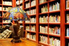Concepto de sitio de lectura de la biblioteca, de lámpara de mesa del vintage, de libros y de estante viejos en biblioteca Fotos de archivo libres de regalías
