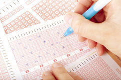 Concepto de Succes - número de marca de la mano del ` s de la persona en boleto de lotería con la pluma Fotos de archivo libres de regalías