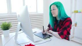 Concepto de trabajar independientemente o de trabajo de oficina Diseñador gráfico de sexo femenino joven con el pelo coloreado qu almacen de metraje de vídeo