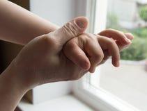 Concepto de una familia feliz - un adulto lleva a cabo la mano de un bebé Imagen de archivo libre de regalías