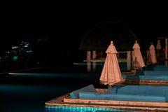 Concepto de una noche del centro turístico Paraguas doblados del sol al borde de la piscina al aire libre de la noche foto de archivo libre de regalías