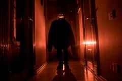 Concepto de Víspera de Todos los Santos Silueta espeluznante en el pasillo oscuro con la cabeza de la calabaza Luz entonada con n fotografía de archivo libre de regalías