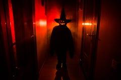 Concepto de Víspera de Todos los Santos Silueta espeluznante en el pasillo oscuro con la cabeza de la calabaza Luz entonada con n imagen de archivo libre de regalías