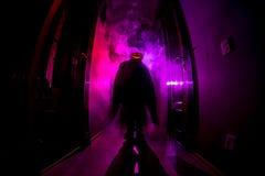 Concepto de Víspera de Todos los Santos Silueta espeluznante en el pasillo oscuro con la cabeza de la calabaza Luz entonada con n fotos de archivo libres de regalías