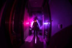 Concepto de Víspera de Todos los Santos Silueta espeluznante en el pasillo oscuro con la cabeza de la calabaza Luz entonada con n imagen de archivo