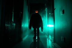 Concepto de Víspera de Todos los Santos Silueta espeluznante en el pasillo oscuro con la cabeza de la calabaza Luz entonada con n fotos de archivo