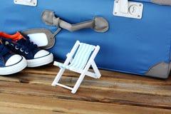 Concepto de vacaciones de verano con la maleta del vintage y la silla de cubierta miniatura en fondo de madera Foto de archivo