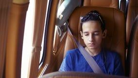 Concepto de vacaciones de verano, viaje paseos adolescentes del muchacho en un minivan con los auriculares almacen de metraje de vídeo
